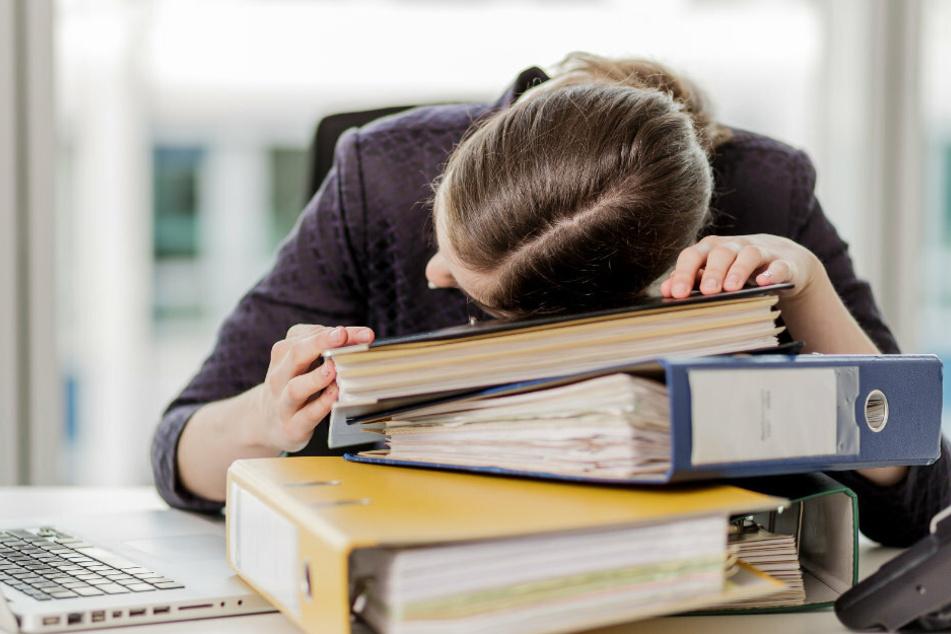 Eine Frau hat ihren Kopf auf die Unterlagen auf ihrem Schreibtisch gelegt. Wer jede Nacht wach liegt, ist tagsüber ständig übermüdet und unkonzentriert. Chronische Schlafstörungen können darüber hinaus Krankheiten auslösen.