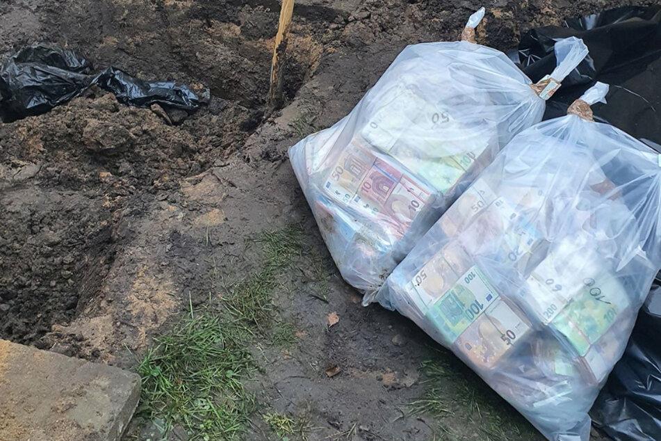 Zwei Säcke mit Geld liegen neben einem Erdloch. Die Scheine wurden vom BKA aus dem Boden geholt und neu verpackt.