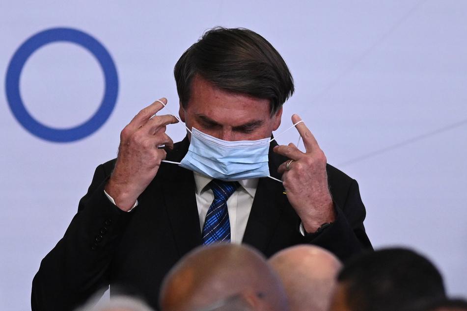 Jair Bolsonaro, Präsident von Brasilien, trägt auf einer Veranstaltung im Präsidentenpalast eine Schutzmaske.