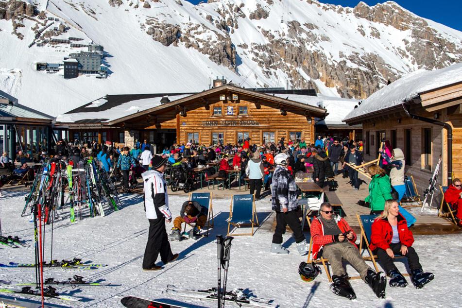 Skifahrer genießen vor einer Hütte in Garmisch-Partenkirchen das gute Wetter. (Archiv)