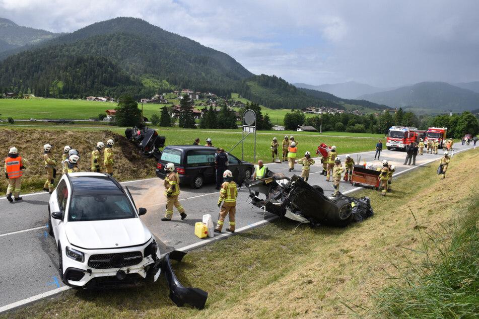 Zahlreiche Rettungskräfte sind an der Unfallstelle bei Achenkirch an einer Straße nahe der Grenze zu Deutschland im Einsatz.