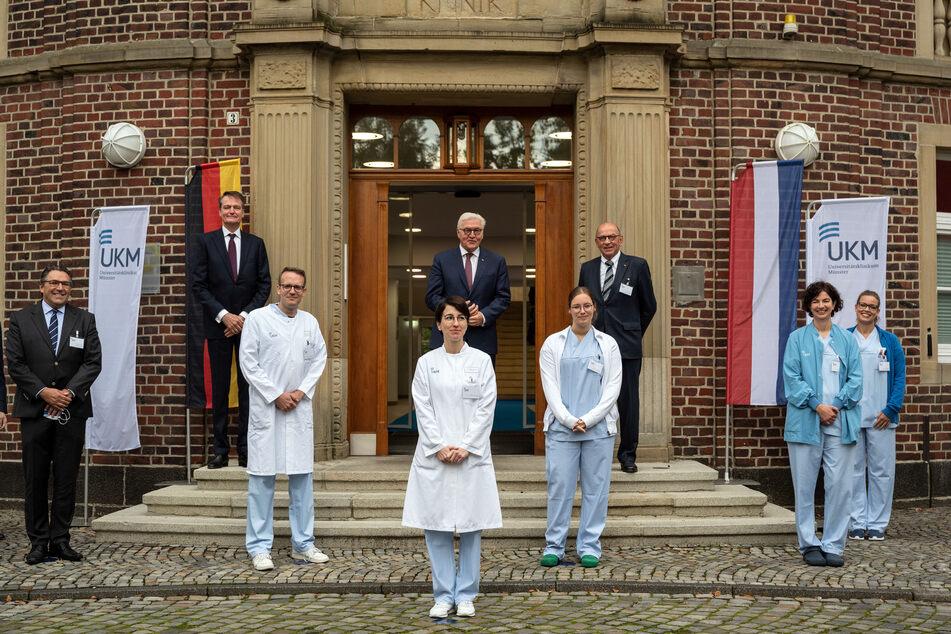 Bundespräsident Frank-Walter Steinmeier steht vor einem Gebäude der Uniklinik zwischen Ärzten und Pflegekräften für ein Gruppenfoto mit Abstand. Der Bundespräsident wollte sich mit seinem Besuch für den Einsatz des Personals in der Corona-Pandemie bedanken.