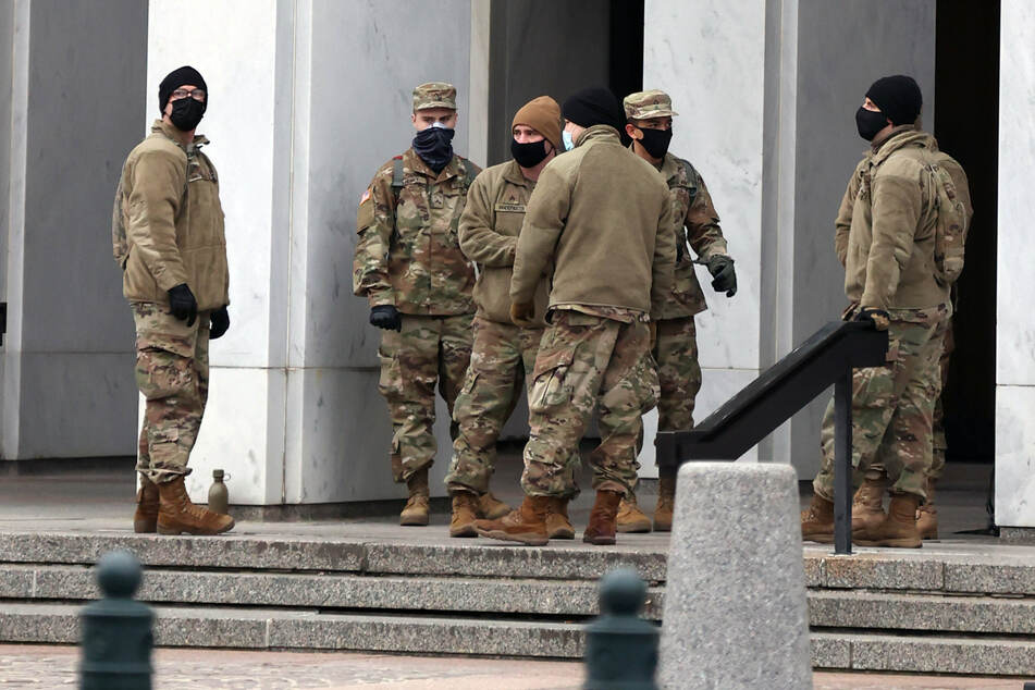 Police and National Guard stand watch over the United States Capitol building.