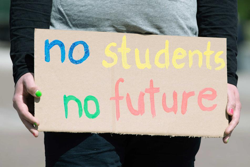 """Eine Studentin trägt ein Schild, auf dem """"no students – no future"""" steht."""