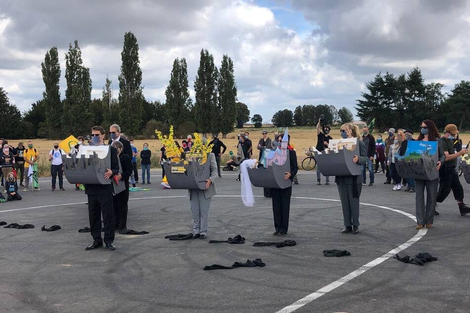 Teilnehmer der Demo zeigen beispielhaft auf, was für den Kohleabbau in der Region weichen musste.