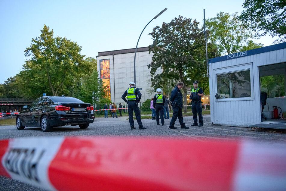 Mehrere Polizeibeamte und Zivilisten stehen nach dem Angriff vor der Synagoge.