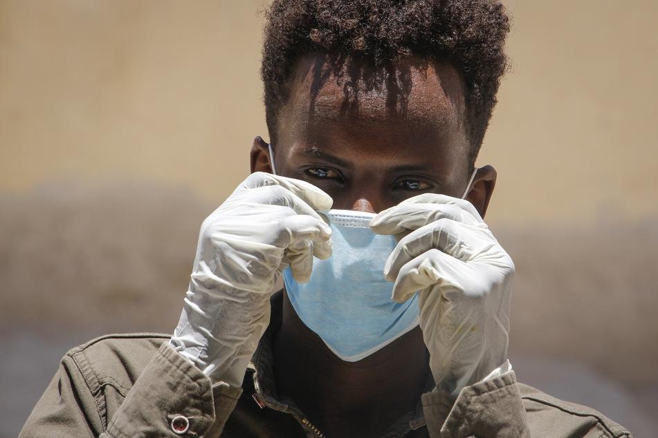 Ein Mann trägt eine chirurgische Maske und Handschuhe auf der Straße.