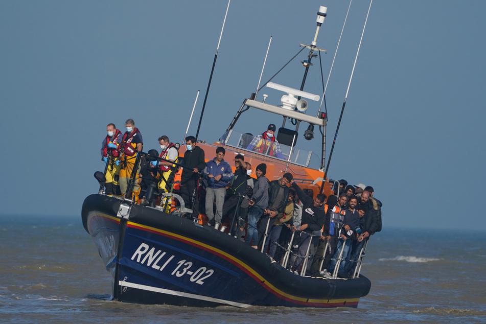 Eine Gruppe vermutlicher Migranten wird nach einem Zwischenfall mit einem kleinen Boot im Ärmelkanal mit einem Rettungsboot an Land gebracht.