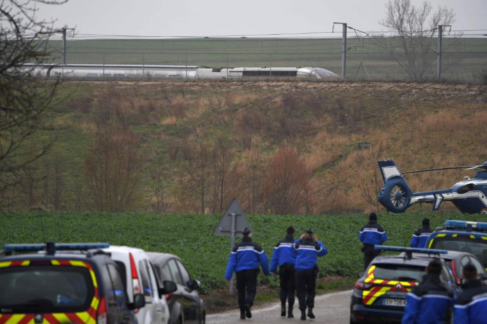 Französische Polizisten treffen in der Nähe der Gleise ein, an dem ein TGV-Hochgeschwindigkeitszug nördlich von Straßburg teilweise entgleist ist.