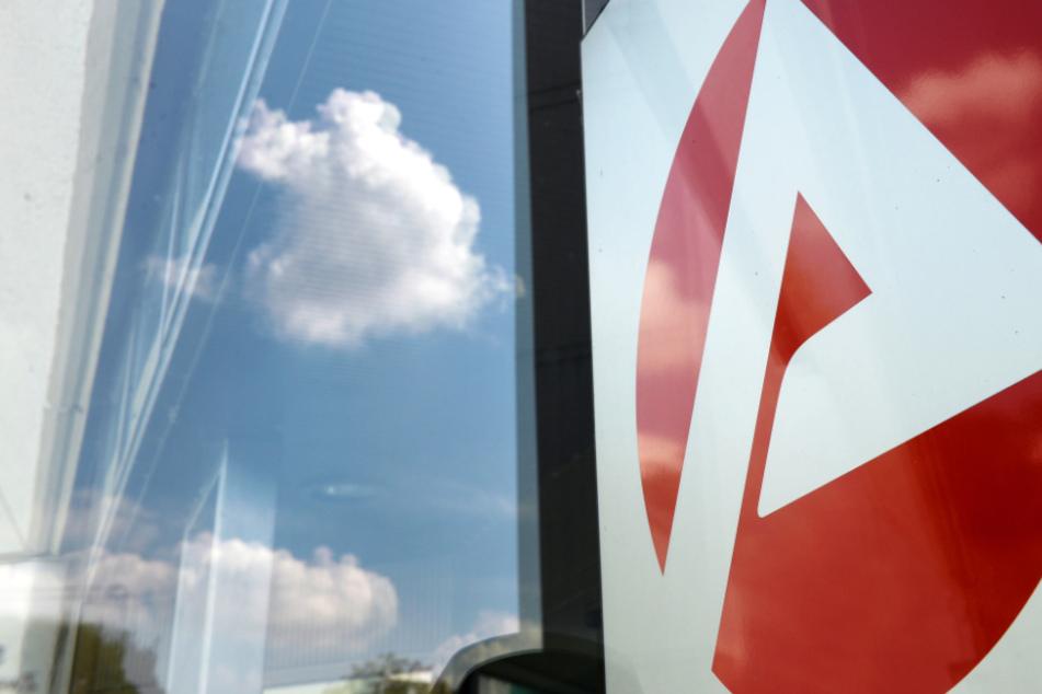 Das Logo eines Jobcenters spiegelt sich in einer Glastür: Wie schwer hat die Corona-Krise den Arbeitsmarkt in Hessen getroffen?