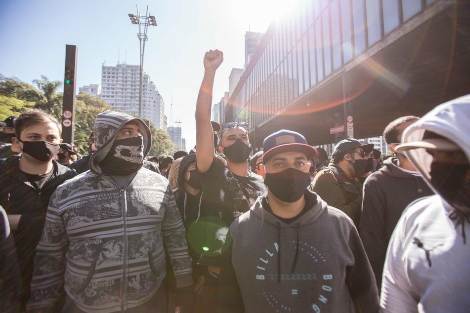 """Ein Teilnehmer eines regierungskritischen Protests auf der Avenida Paulista streckt seine Faust in die Luft. Die Zahl der Corona-Toten in Brasilien steigt weiter rasant an. Brasiliens rechtspopulistischer Präsident Bolsonaro hält die Lungenkrankheit für eine """"leichte Grippe"""" und lehnt Schutzmaßnahmen ab."""