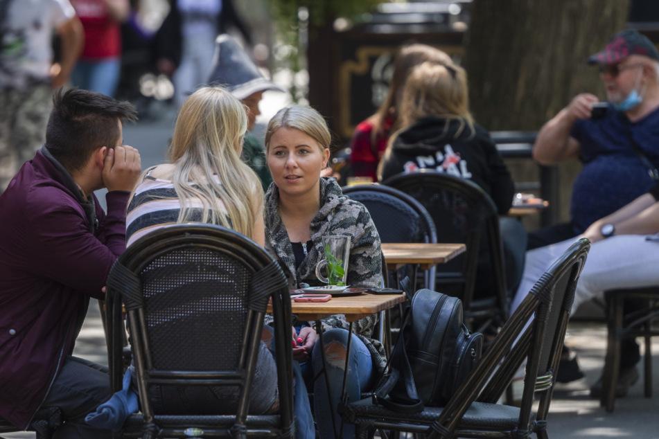 Bratislava: Gäste sitzen in kleinen Gruppen an Tischen im Außenbereich eines Cafés.