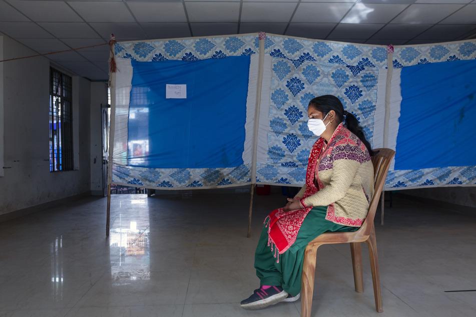 Indien, Dharmsala: Eine Freiwillige sitzt vor einem Beobachtungsraum auf einem Stuhl, nachdem sie an einer Corona-Testimpfung teilgenommen hat. In Indien soll am 16.01.2021 eine der weltweit größten Corona-Impfkampagnen beginnen.