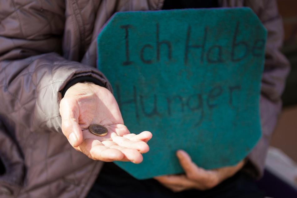 """Eine Frau bittet in Hamburg mit einem Schild mit der Aufschrift """"Ich habe Hunger"""" um Spenden."""