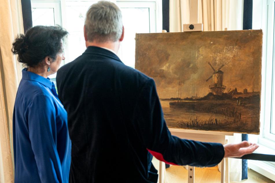 Zwei Interessenten sehen sich das Gemälde an.