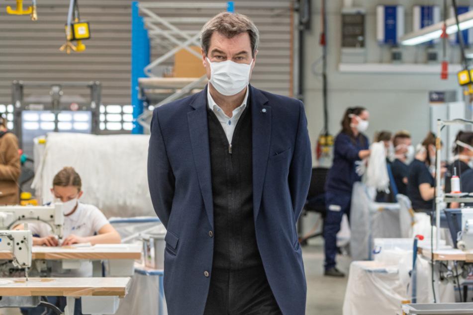 Markus Söder (CSU), Ministerpräsident von Bayern, steht in einer Produktionshalle des Automobilzulieferers Zettl, der nun Masken herstellt.