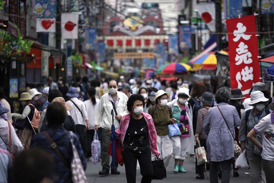 Konsumenten gehen über eine Einkaufsstraße in Tokio.
