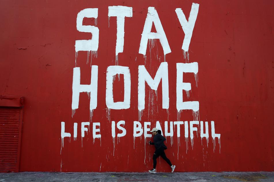 """Ein Jogger läuft an einem Wandbild mit der Aufschrift """"Stay Home - Life is beautiful"""" (""""Bleib zu Hause, das Leben ist schön"""") vorbei."""