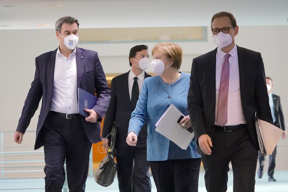Bundeskanzlerin Angela Merkel (66, CDU) kommt neben Markus Söder (54, CSU, l.), Ministerpräsident von Bayern und CSU-Vorsitzender, und Michael Müller (56, SPD, r.), Regierender Bürgermeister von Berlin, zu der Pressekonferenz nach dem Impfgipfel im Kanzleramt.