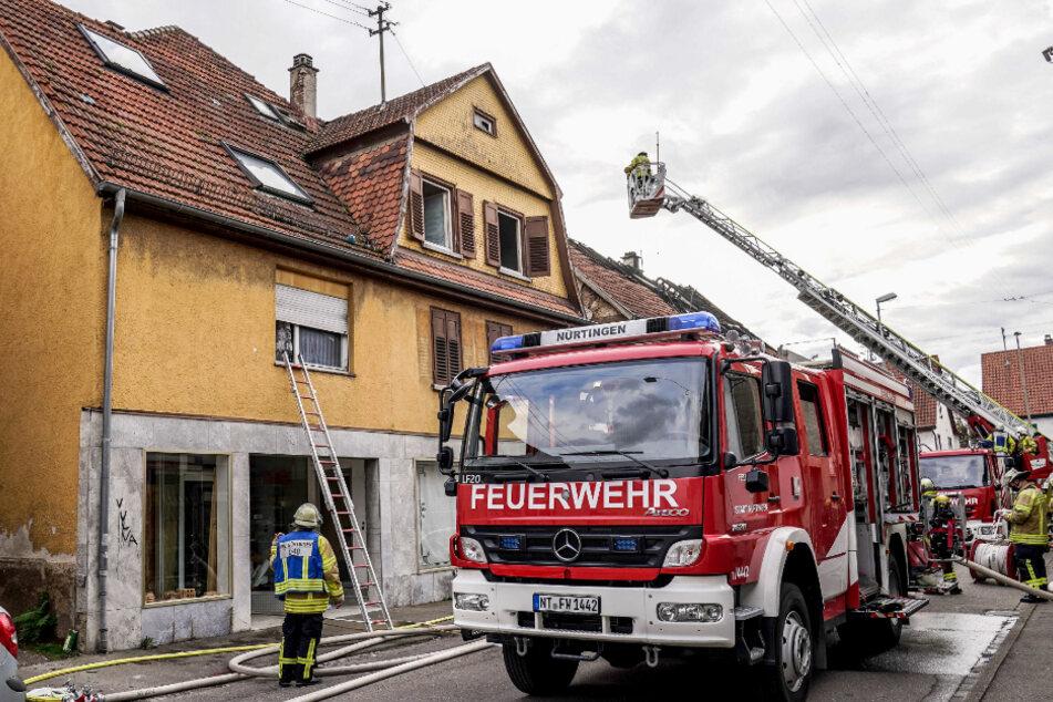 Einsatzkräfte der Feuerwehr und des Rettungsdienstes arbeiten an einem Brand in einem Wohnhaus. Zuvor hatte es im Nachbargebäude gebrannt.