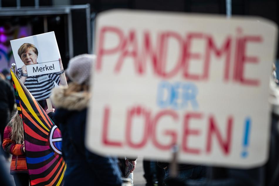 """""""Pandemie der Lügen!"""" steht auf dem Schild eines Teilnehmers geschrieben, der an einer Demonstration gegen die Corona-Politik der Bundesregierung teilnimmt. Im Hintergrund ist ein Schild zu sehen, auf dem Bundeskanzlerin Merkel in Sträflingskleidung abgebildet ist."""