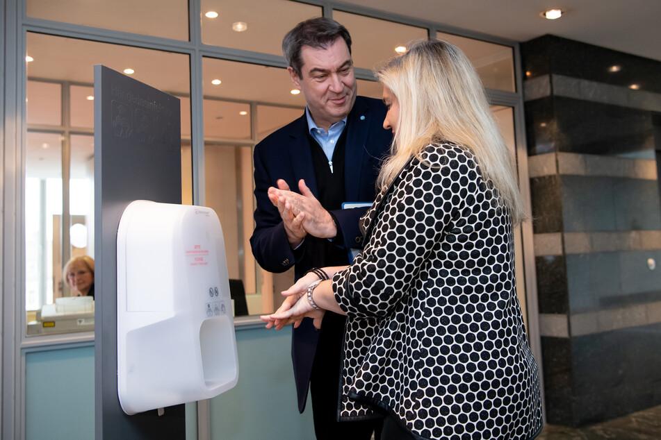 Markus Söder (CSU), Ministerpräsident von Bayern, und Melanie Huml (CSU), Gesundheitsministerin von Bayern, desinfizieren sich vor Beginn einer Sitzung des bayerischen Kabinetts die Hände.