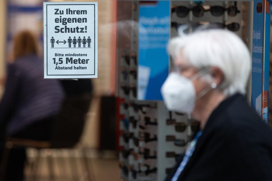 Eine Frau mit Mundschutz geht an einem Geschäft vorbei.