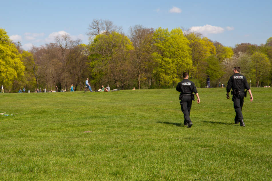 Zwei Polizisten gehen durch den Englischen Garten im Herzen der Stadt. Das sonnige Wetter hat am Karsamstag erneut viele Menschen ins Freie gelockt, die Polizei hat über die Ostertage ihre Kontrollen wegen der Corona-Krise verschärft.