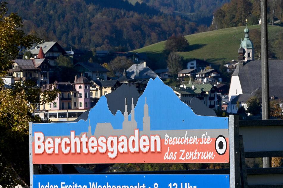 """Ein Schild mit der Aufschrift """"Berchtesgaden - Besuchen Sie das Zentrum"""" hängt vor der Kulisse der Ortschaft."""