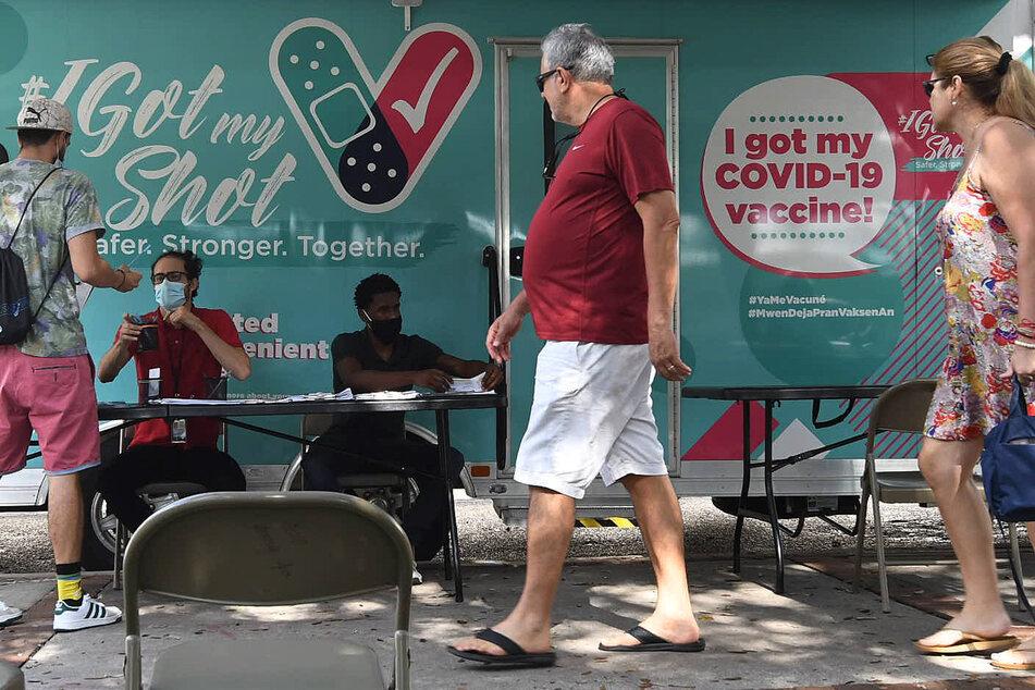 USA, Orlando: Menschen kommen melden sich an einer mobilen Corona-Impfstelle an.