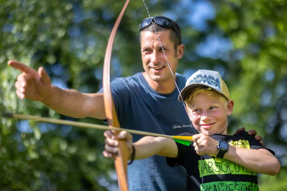 Erlebnispädagoge Hendrik Hadlich (43) übt mit Theo (8) Bogenschießen.