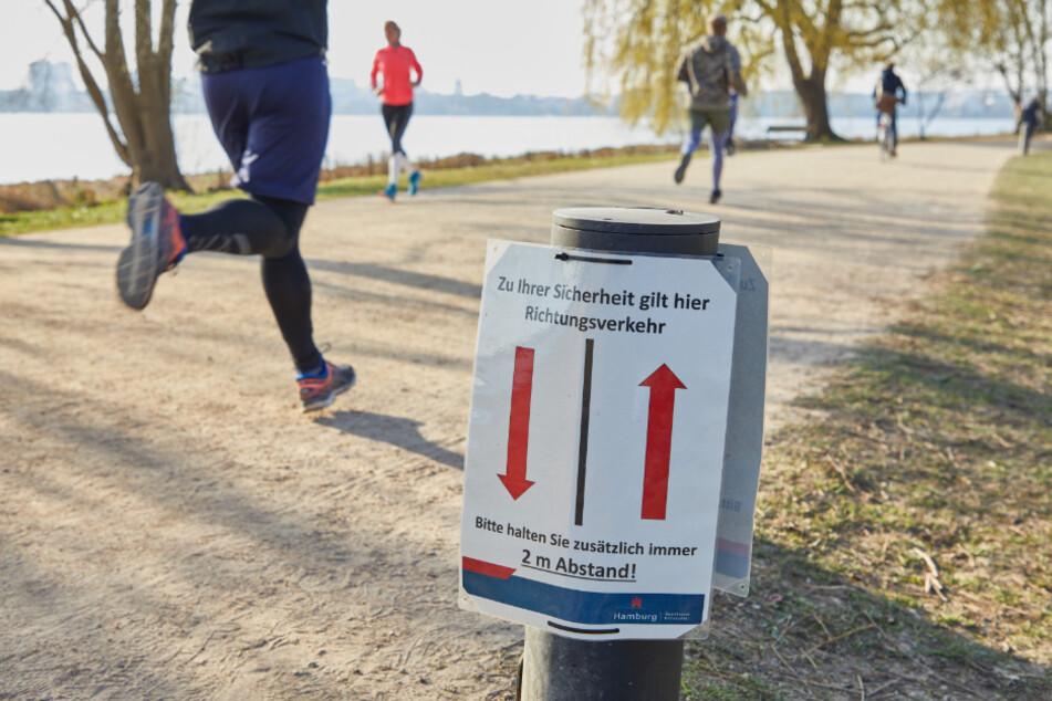 Jogger laufen an der Außenalster an einem Hinweisschild des Bezirksamtes Eimsbüttel vorbei.