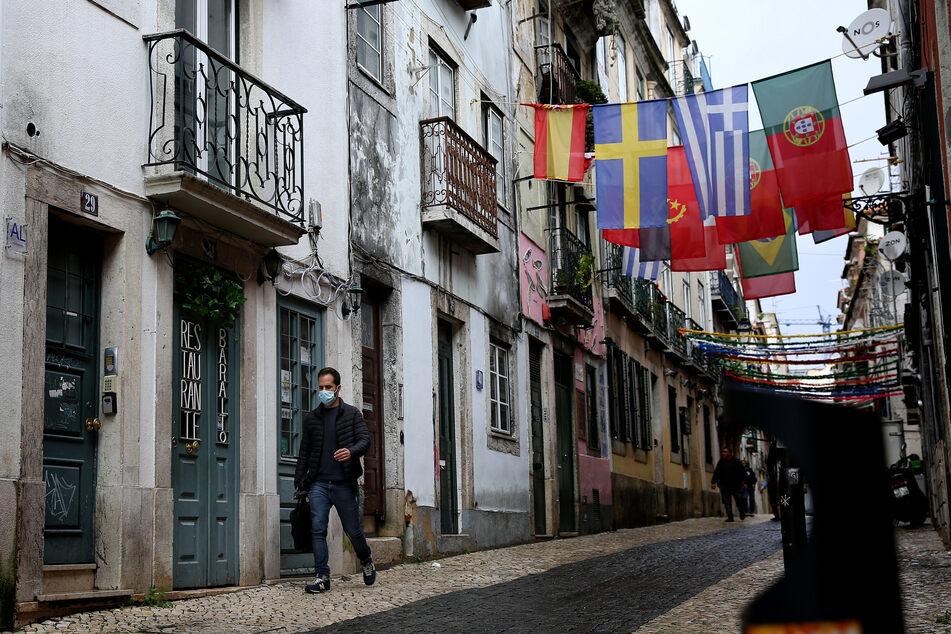 Ein Mann geht inmitten der Corona-Pandemie durch eine einsame Straße in Lissabon.