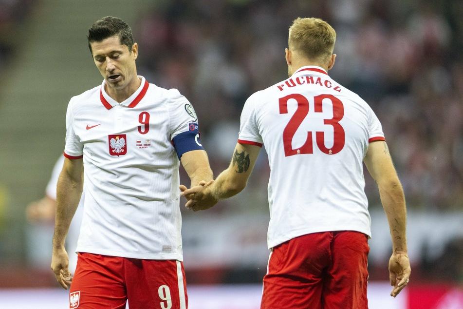 Tymoteusz Puchacz (r.) klatscht im WM-Spiel gegen England mit Teamkollege Lewandowski ab.