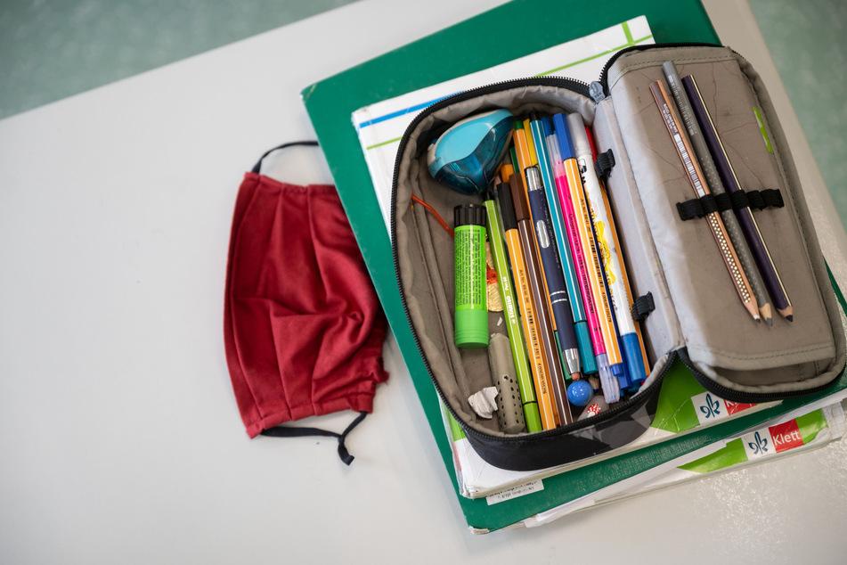 Eine Mund-Nasen-Bedeckung liegt während einer Unterrichtsstunde neben einem Mäppchen und Schulbüchern auf einem Schultisch.