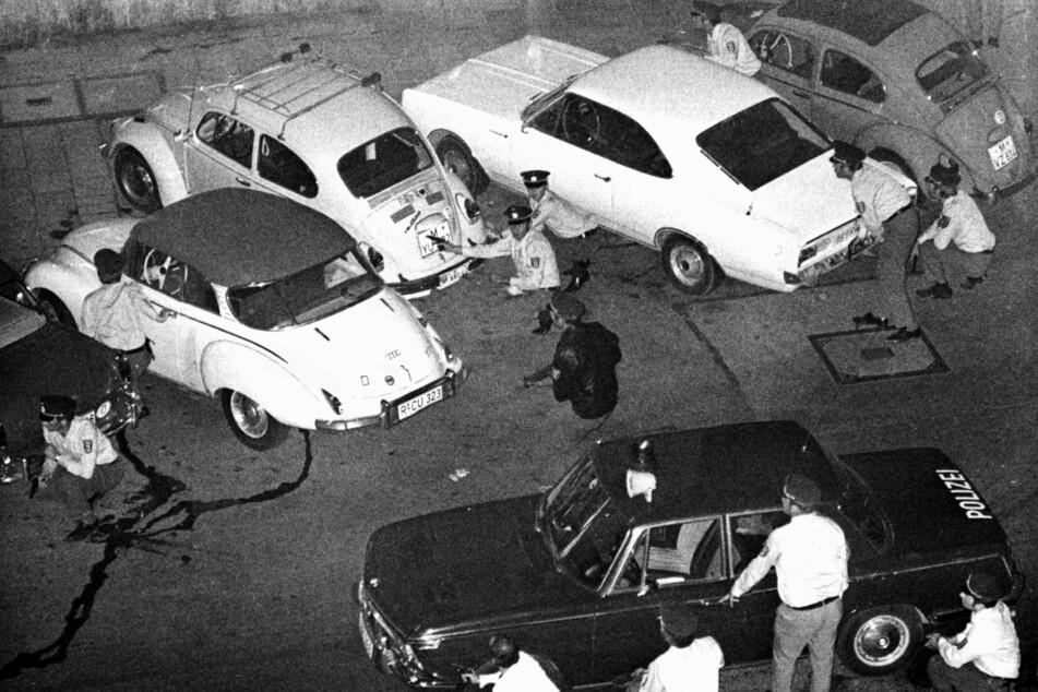 Wie sieht das richtige Vorgehen aus? Bewaffnete Polizisten schützten sich in München gegenüber der Deutschen Bank hinter Autos.