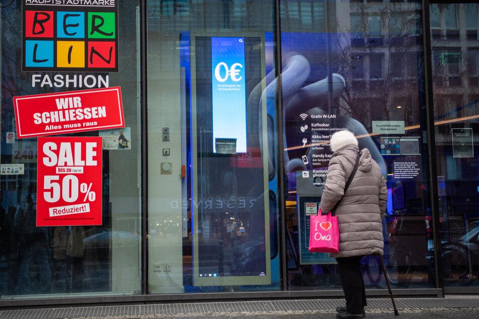 Eine alte Frau mit einer Tasche blickt in ein Schaufenster in Berlin.