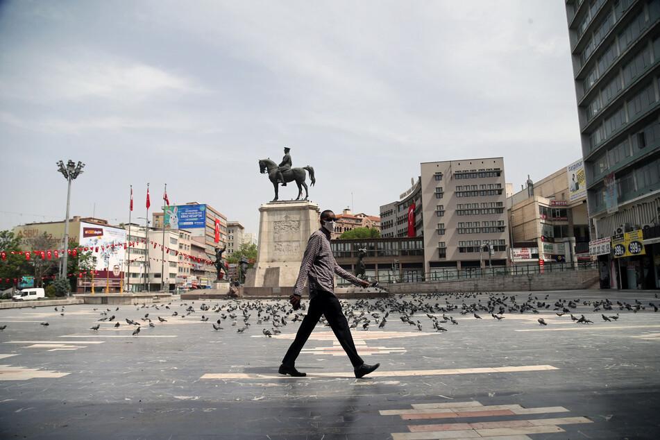 in Mann mit einer Maske geht über den leeren Ulus-Platz in Istanbul.