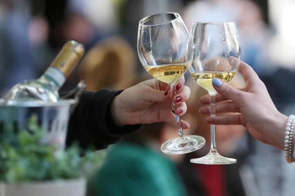 Gäste stoßen an einem Tisch im Außenbereich eines Lokals mit Weißwein an.