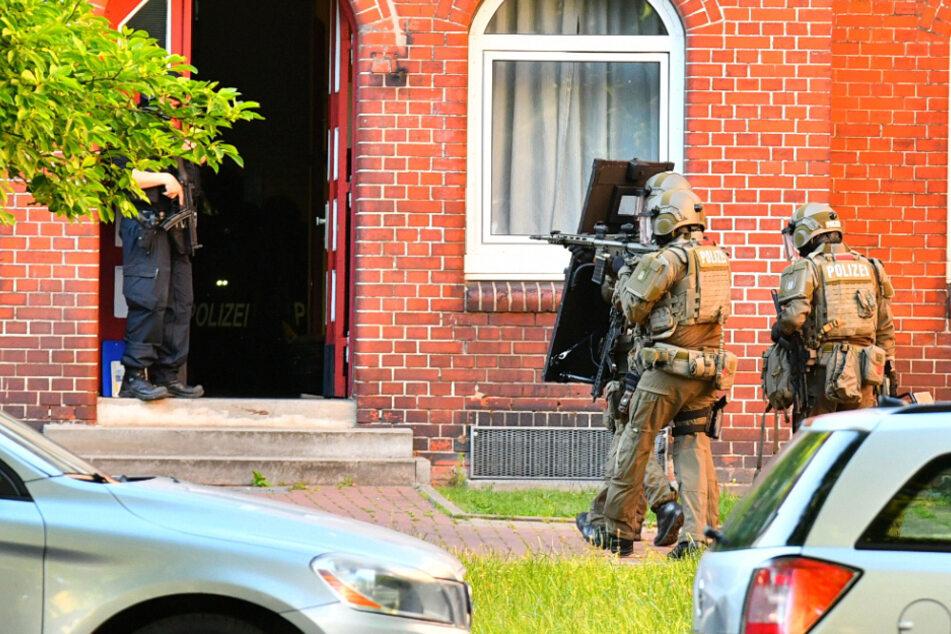 Mit Waffe im Anschlag gehen SEK-Beamte auf ein Haus in Hamburg-Wilhelmsburg zu.