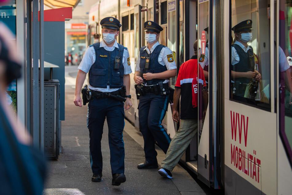 Würzburg: Zwei Polizisten steigen an einer Tram-Haltestelle aus der Straßenbahn aus.