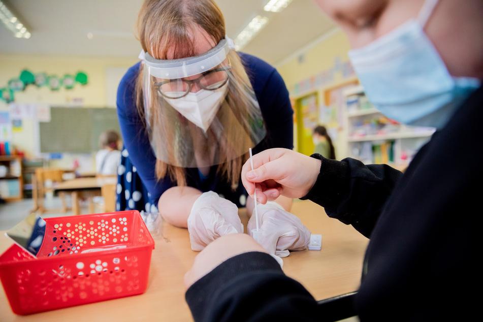 Eine Lehrerin unterstützt einen Schüler bei seinem Corona-Schnelltest in der Grundschule.
