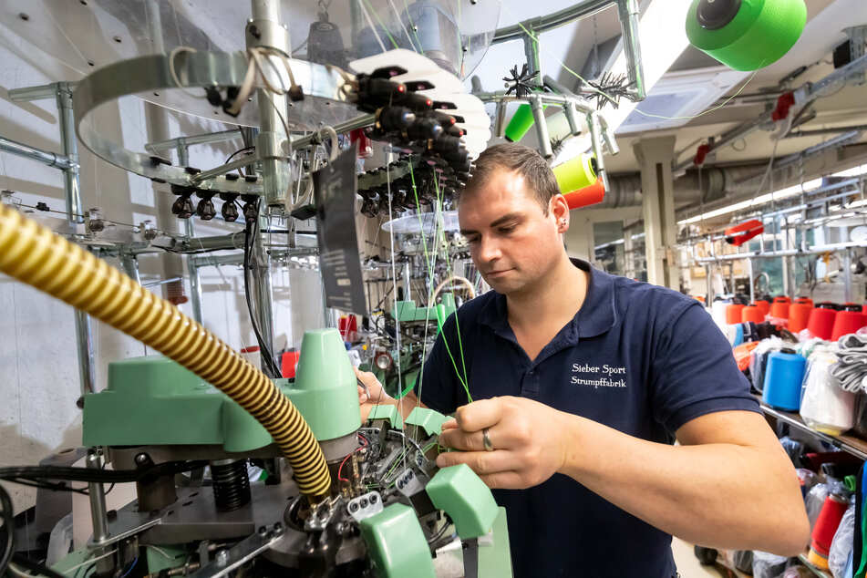 In Großolbersdorf gibt es Socken und Strümpfe mit Firmenlogos: Firmenchef Denny Sieber (33) richtet eine Rundstrickmaschine ein.