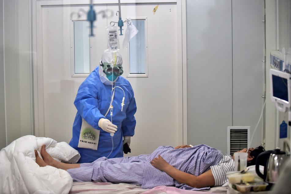 16.06.2020, China, Peking: Eine Krankenschwester behandelt eine COVID-19-Patientin auf einer Isolierstation im Beijing Ditan-Krankenhaus. Die chinesische Gesundheitsbehörde teilte mit, dass sie am 15.06.2020 auf dem chinesischen Festland Berichte über 40 neue bestätigte COVID-19-Fälle erhalten habe, von denen 32 im Inland übertragen und acht importiert worden seien. Foto: Peng Ziyang/XinHua/dpa +++ dpa-Bildfunk +++