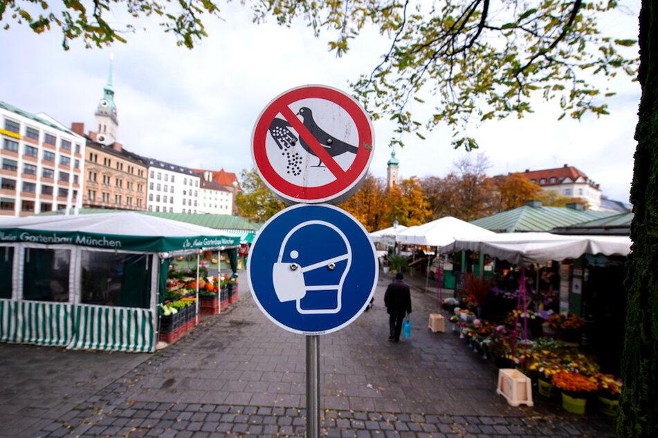 Eine symbolische Darstellung der Maskenpflicht ist auf einem Hinweisschild auf dem Viktualienmarkt in der Innenstadt zu sehen.