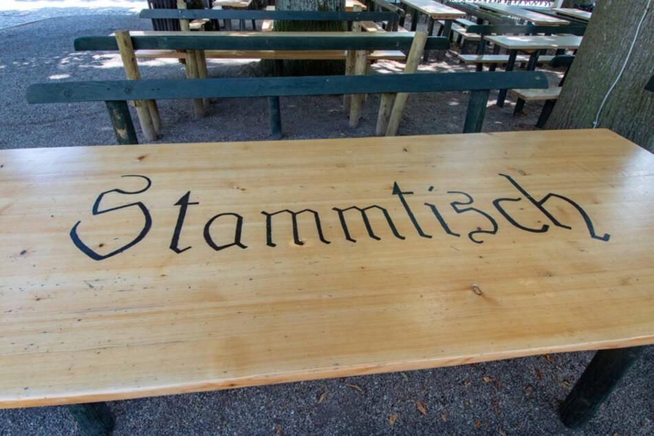 """""""Stammtisch"""" steht auf einem Tisch in einem Biergarten. Auch wenn sich täglich noch Menschen in Bayern an dem neuartigen Coronavirus infizieren, drosselt die Staatsregierung die Gegenmaßnahmen wieder ein wenig herunter."""