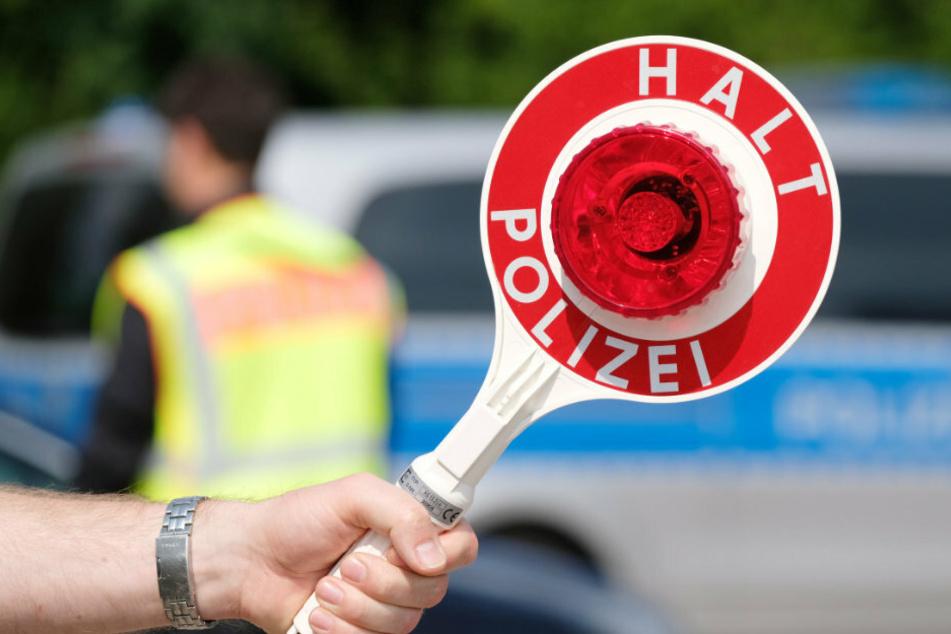 Ein Polizist kontrolliert auf den Straßen in Sachsen die Fahrzeuge. (Symbolbild)