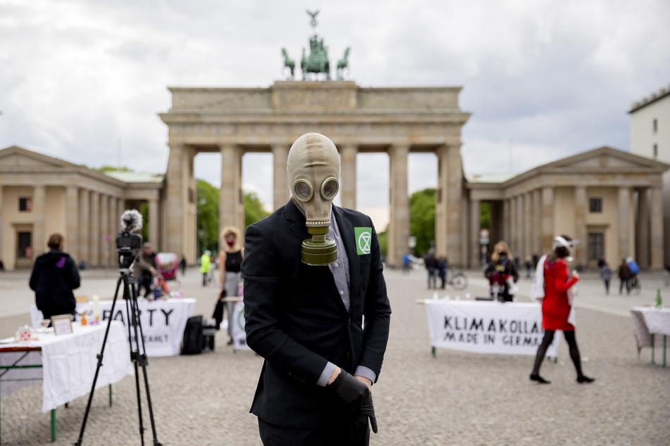 """Berlin: Ein Teilnehmer mit Gasmaske steht vor einer Kundgebung von Extinction Rebellion vor dem Brandenburger Tor. Die Kundgebung fand Anfang Mai zu Beginn der bundesweiten Aktion von Extinction Rebellion anlässlich des """"Earth-Overshoot Day"""", dem """"Welterschöpfungstag"""" statt."""