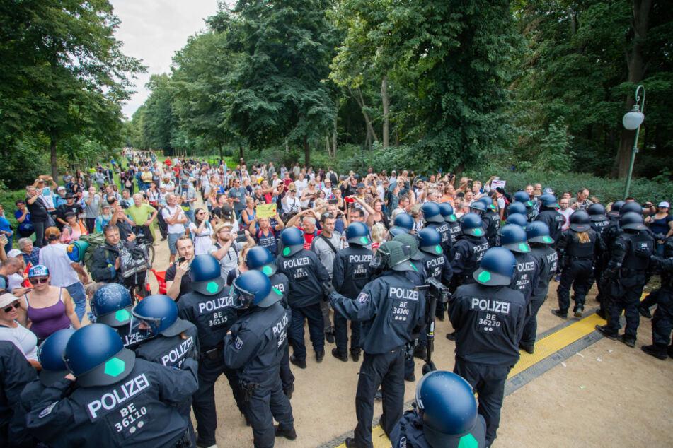 Polizisten drängen bei einem Protest gegen die Corona-Maßnahmen an der Siegessäule Menschen in den Tiergarten ab.