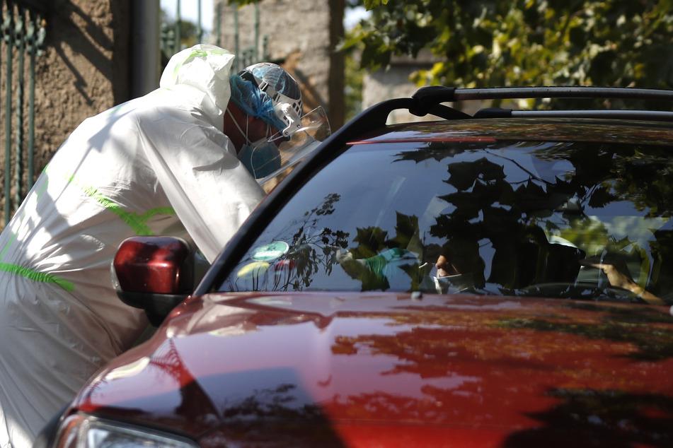 Prag: Ein medizinischer Mitarbeiter in Schutzausrüstung untersucht einen jungen Autofahrer an einer Drive-in-Teststation auf Covid-19-Symptome. In Tschechien breitet sich das Coronavirus weiter rasant aus.